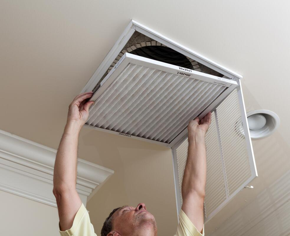 a man changing the filter of air vent